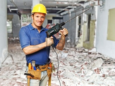 8267326-confident-handyman-with-big-drill-on-duty-at-construction-site